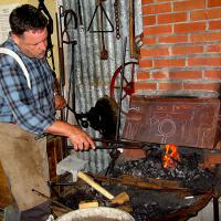 photo of blacksmith working at forge